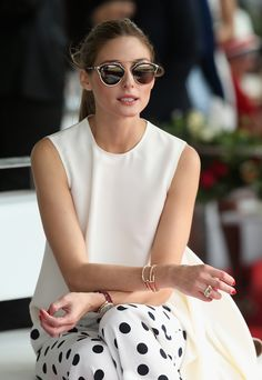 Olivia Palermo wearing white sleeveless top and white trousers with black polka dots