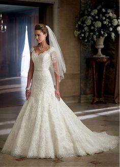 This stunning wedding dress is made of satin inside andtulle outside shaping a v-neck neckline, a deep v-back andlace cap sleeves. The dresshas lace appliques decoratedin the neckline, the bodice and the skirt and with beadings details at the satin sash. The back of the dress iszipper up closure.