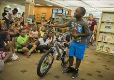PEORIA — Scholarly silence was nowhere to be found at the Lincoln Branch Library Friday morning. Instead, the pulsing rhythm of R&B music filled the airy addition at the historic Carnegie Library as nearly 200 children attended the annual summer reading program bicycle raffle.