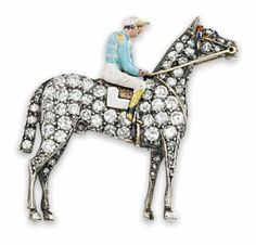 The horse realistically modelled at rest, pavé-set with circular-cut diamonds and an enamel saddle and brow-band, the jockey with painted enamel racing colours, mounted in silver and gold, circa 1890,