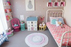 Love the multiple different colored furniture, garland on bed, boxes above bed, book shelves, and the beautiful dollhouse.