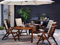 Jardín con unas sillas reclinables marrones con cojines de respaldo y asiento en color beige y una mesa abatible.
