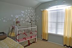 The blue-gray color on the walls is accented with the yellow curtains and the yellow in the fabric on the crib and changing table. The tree on the wall leads your eye to the crib which has red in it. This is a very exciting fun room.