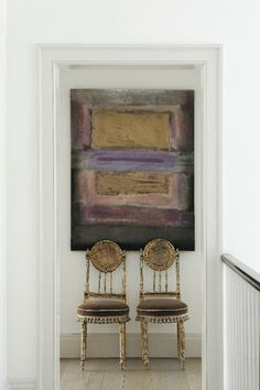 Antique chairs look amazing with this modern painting. Great clean and bright space too!