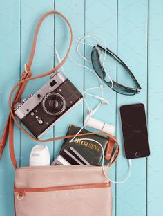 female bag with a variety of personal belongings and with retro camera. set traveler by Mamuka Gotsiridze on @creativemarket