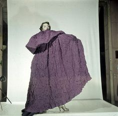 Model is wearing a long mauve cape of 'tissu gaufré' by Elsa Schiaparelli, Spring Collection, 1951