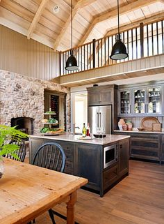 Love this kitchen with stone wall, soaring ceiling and hand-rubbed, stained cabinets.
