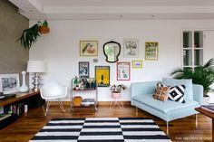 Sala de estar tem parede de cimento queimado, sofá azul claro, tapete listrado e parede galeria.