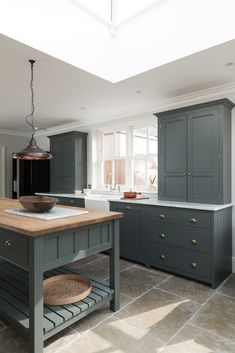 The Hampton Court Kitchen by deVOL painted in a beautiful bespoke paint colour with Umbrian Limestone flagstones throughout.