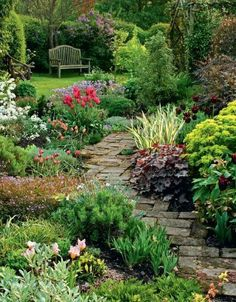 Lovely garden path landscaped with perennial foliage plants, grasses and flowering bulbs. Brick - Bricks