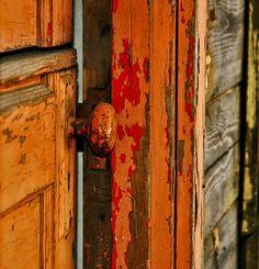 Weathered orange paint on wood door