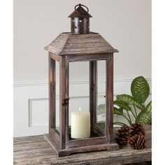 The decorative, Old World style of this lantern features weathered wood with bronze metal accents. Distressed beige candle included.