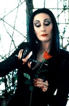 Addams Family Values. Such a classy way of cutting for flowers arrangement there Morticia :))