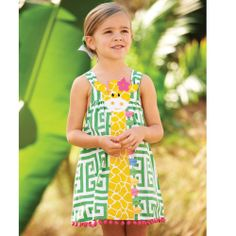 Patterned dress features oversized giraffe applique bodice and pom-pom hem.   Straps tie in bow at back.