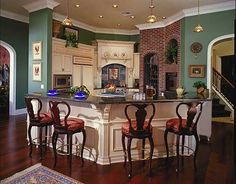 A bright, yet small kitchen with brick accents on one wall of the curved kitchen. The white cabinetry is lightly distressed for a country-style.
