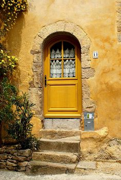 Portal em arco pleno com com escadaria e porta amarela com visor e cortina.