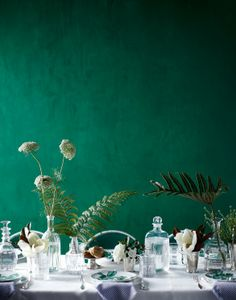 Ferns and foliage in vases. What a lovely, surprise. And that emerald green wall? Just a verdant dream!
