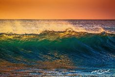 The sun sets shining through the majestic ocean waves. The water has a beautiful orange and turquoise glow as it crashes into the sea. Taking a deep breath of the salty beach air around peace and joy fill our hearts of the amazing scene unfolds.