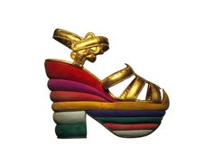 "Ferragamo 'Rainbow' Sandal - made in 1938 for Judy Garland (the shoe is almost 5"" high and made of strips of coloured suede).  **A lack of raw materials after the Great Depression led a resourceful Ferragamo to come up with the cork and wood wedge - so innovative that it became the first piece of fashion design to be patented.**"