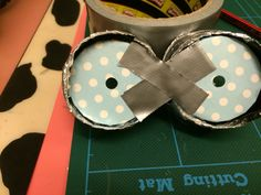 Step 08: Attach left and right sides of frames with masking tape. Use double-sided sticky tape to attach cupful liner bases into inside of minion google's frame