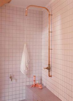 Zewnętrzna instalacja w łazience prysznica w formie grubej miedzianej rurki bez deszczownicy