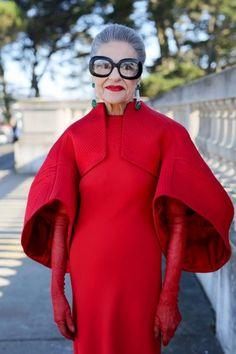 Met een statement bril, rode lippenstift en matching knalrode designer outfit lijkt dit omaatje recht uit de set van The Devil Wears Prada te komen.