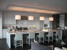 Kelly Deck Design  Stunning kitchen with creamy white shaker kitchen cabinets, marble countertops, pot filler, marble kitchen island, gray, leather, counter stools, drum pendants, walnut stained butler's pantry with marble slab backsplash and wine fridge.