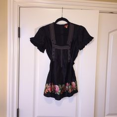 Free People top Free People top in black with lace trim detail on the front and floral pattern around the bottom. Button detailing on the front and buttons down the back. Tie in back. EUC. Worn only once. Free People Tops Blouses