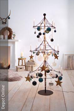 Wer eine Alternative zum Weihnachtbaum sucht, kann stattdessen auf ein Gestell aus Metall mit Christbaumkugeln und Sternanhängern zurück greifen. Eine Lichterkette komplettiert den Look.