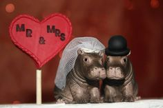 ***Happy Happy Hippos***  Please Note: The pair pictured here are pre-molded plastic, and as such this particular version is not alterable, apart from the accessories. Heart topper is not included, but can be ordered separately.  THE ORDER Want to switch the accessories around? I can do that! The veil and hat -- are completely customizable; go ahead and let me know your wedding colours and Ill design them to match. Order includes two pre-molded plastic figures and your choice of accompanying…