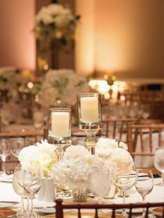 Chic white floral wedding reception centerpiece with romantic candles; Featured Photographer: Pamela Hults Photography