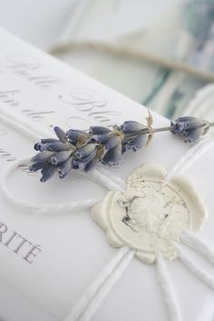 White wax seal over string with a tiny sprig of lavender - white printed paper wrap: Love the wax seal idea for wedding invitations!