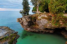 Early morning long exposure photo at Door County, Wisconsin's Cave Point, on Lake Michigan, Reveals rocky cliffs, colorful waters, and a cloudy sky.