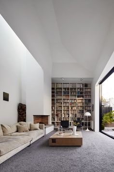 open plan living room with floor-to-ceiling bookcase | House 3, by Coy Yiontis Architects