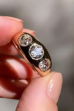 Antique gypsy ring centering a trio of old European diamonds approx. 1.76 carats (.48, .72, .56) flush-mount in 14k yellow gold. Center: 8.4 x 16.5mm, band: 2.8 - 4.3mm. Circa 1900.