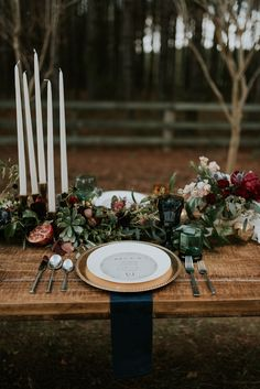 Tall white candlesticks, long wooden tables, succulents and fruit, dark blue napkins, eclectic green glassware, ethereal outdoor wedding reception placesetting, red florals //Moriah Elisabeth