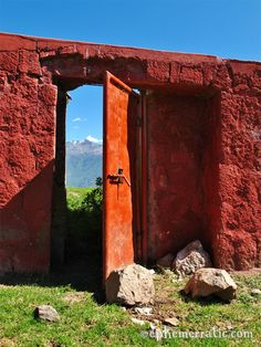 View of volcanic mountains through a red door at a bull ring in the remote village of Cabanaconde in Colca Canyon, Peru.