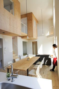 リビングを中心に、2F居室が箱で出現させた、シンプルな空間を設計。吹き抜けと、南側に大きな開口を設け、豊かな緑の借景を実現。