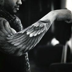 noch ein mann mit einem schönnen schwarzen tattoo   hier ist ein engel tattoo mit einem engelsflügeln mit weißen federn