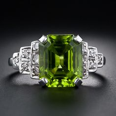 A carat emerald-cut peridot is embraced in classic Art Deco style. The vibrant lime green gemstone is set with three tiers of diamonds stepping down each shoulder, and is set with four prongs atop a scrolled gallery with both engraved and milgrain de Art Deco Ring, Art Deco Jewelry, Vintage Jewelry, Fine Jewelry, Geek Jewelry, Antique Jewelry, Art Deco Schmuck, Peridot Jewelry, Peridot Rings