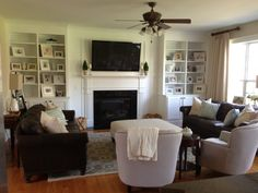 Large White Wooden Bookcase With Fireplace And Black Led Tvon Top Added By Dark Brown Leather Couch And White Chair Also Grey Areas Rug On Laminate Flooring In White Living Room