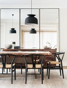 This room exudes beauty in functionality. A minimalist dark grey pendant light, mirrored walls, natural wood table and serving bar and dark grey rattan sculptural chairs.