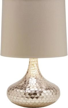 The silver bottleneck glass Tortoise Table Lamp from Arteriors Home with its beautiful reflective surface gives the effect of tortoise shell-patterned mirrored tiles. The hammered base topped with a putty colored shade with silver foil lining makes this lighting accessory a must-have for your beach house, sunroom, office or living room.
