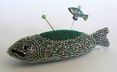 """The fish pincushion is bead embroidery. It measures 3 1/4"""" long by 3/4"""" wide. It is stitched on gray Ultra Suede. My inspiration for this piece was an antique sterling silver fish pincushion in my collection of antique sewing tools."""