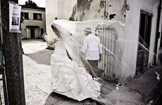 A bride's long veil and trail danced behind her on the streets of Sicily, Italy. - Flickr user ttan_
