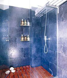 Las paredes de la ducha de obra se revistieron con pizarra, y el suelo se cubrió con lamas de madera de teca.