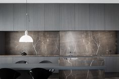 Kitchen with dark wood and Moon Grey marble by Arjaan De Feyter. Photo by Thomas De Bruyne.