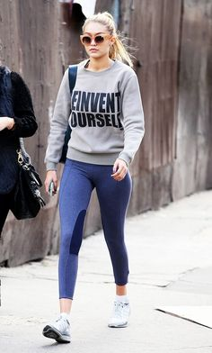 Gigi Hadid looks ultra stylish post-gym in her graphic pullover and flirty peach sunglasses.