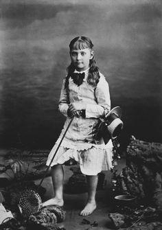 Princesa Alix de Hesse em pé sobre uma 'praia', olhando para frente. Ela possui rede de pesca, e tem o chapéu pendurado em seu braço esquerdo. Usa um vestido de mangas compridas; e está descalça. Julho de 1878.