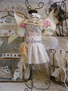"adorned w/ fairy wings & a banner w/ ""beautiful fairy"" written in French"